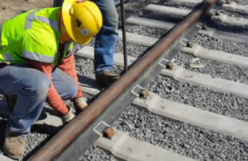 Construction workers installing rail boots